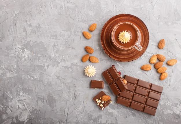 Taza de chocolate caliente y trozos de chocolate con leche con almendras sobre un fondo de hormigón gris