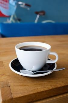Taza de cofffee negro en la tabla de madera, café de la mañana.