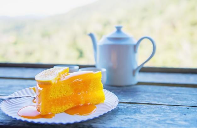 Taza de comer caliente y pastel de naranja con fondo verde de la naturaleza