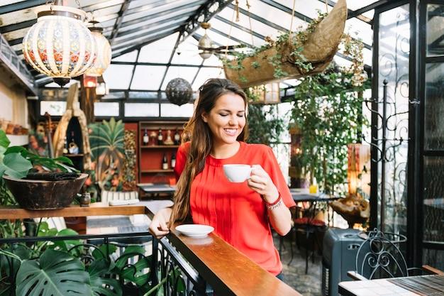 Taza de consumición feliz de la mujer de café en café