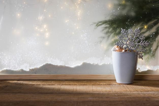 Taza con copo de nieve de juguete en una mesa de madera cerca del banco de nieve, luces de colores y ramita de abeto