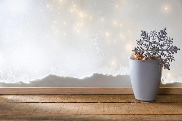 Taza con copo de nieve de juguete en la mesa de madera cerca del banco de nieve y luces de colores