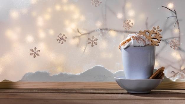 Taza con copo de nieve de juguete en un plato con galletas en la mesa de madera cerca del banco de nieve y luces de colores