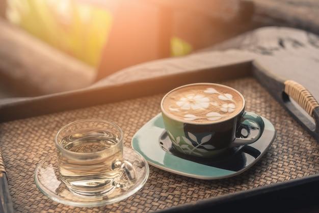 Taza de cristal del café caliente en la tabla de madera en cafetería con el fondo natural verde.