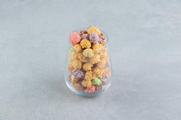 Una taza de cristal llena de dulces palomitas de maíz multicolores.