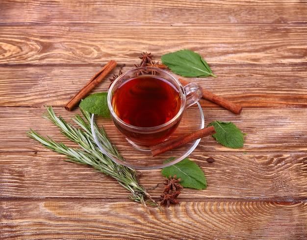 Taza de cristal de té verde con canela sobre un fondo de mesa de madera.