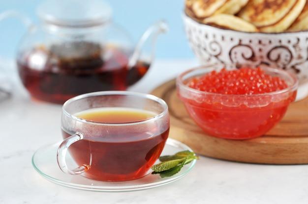 Taza de cristal transparente con té negro y menta sobre panqueques y caviar