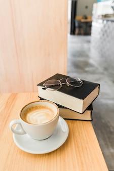 Taza de café con diario y gafas en el escritorio de madera
