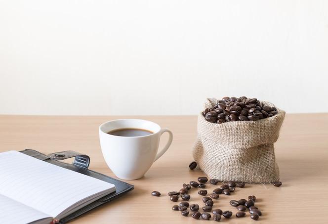Taza de café con granos de café colocados en una mesa de madera