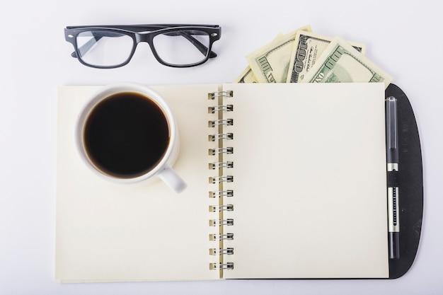 Taza de café en el cuaderno con gafas en el escritorio