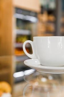 Taza de café en el mostrador de café reflectante