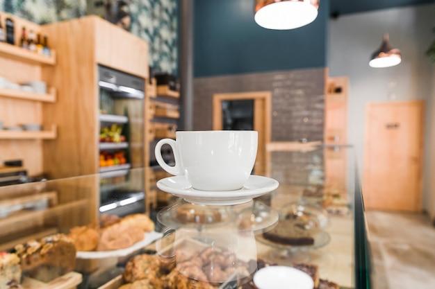 Taza de café en el mostrador de vidrio
