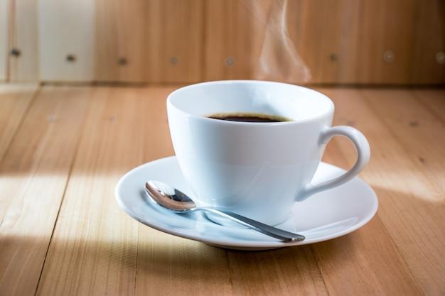 Taza de café negro caliente con los granos de café tostados