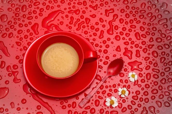 Taza de café roja y flores pequeñas en blackground rojo