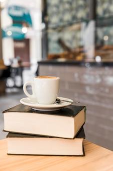Taza de café sobre libros en la mesa de madera