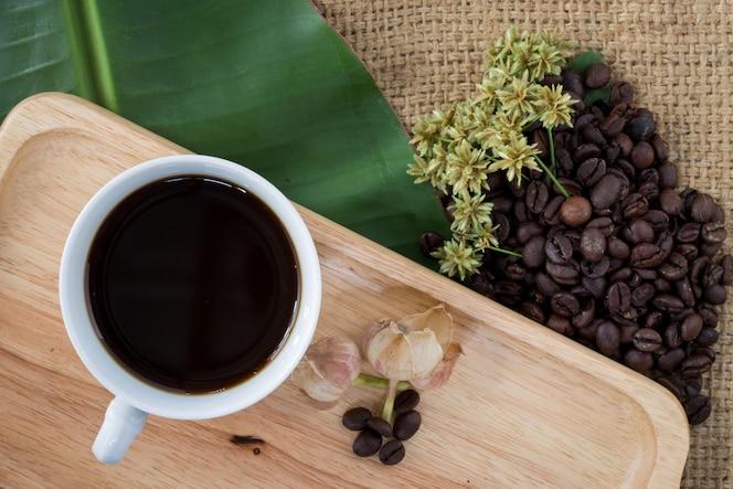 Taza de café sólo y granos de café en fondo de madera.