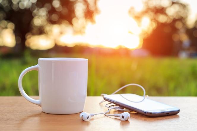 Taza de café y teléfono inteligente en la mesa en el atardecer