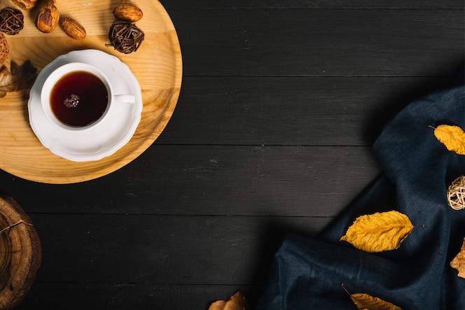 Taza de té cerca de la tela con hojas
