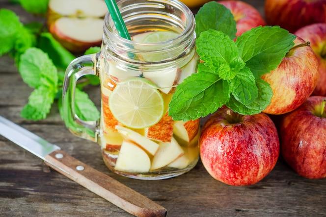 Taza deliciosa bebida refrescante de frutas de manzana con menta en agua infundida de madera