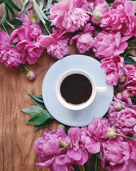 Una taza de delicioso café y muchas peonías.