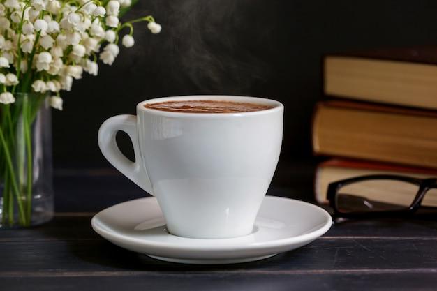 Taza de delicioso café. ramo de lirios del valle, viejos libros antiguos y vasos están detrás