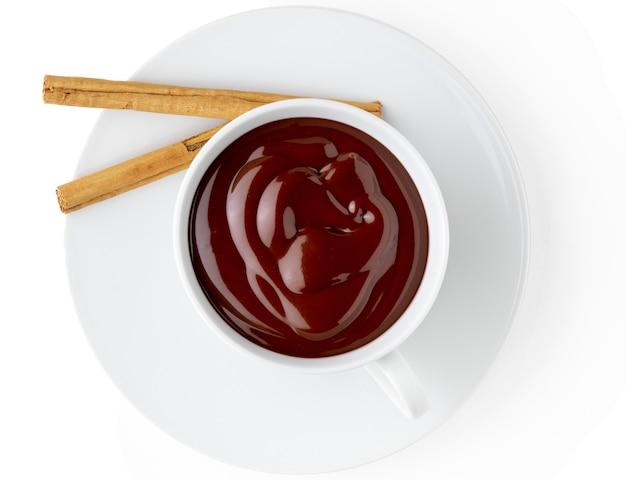 Taza de delicioso chocolate caliente bebible espeso con canela en rama