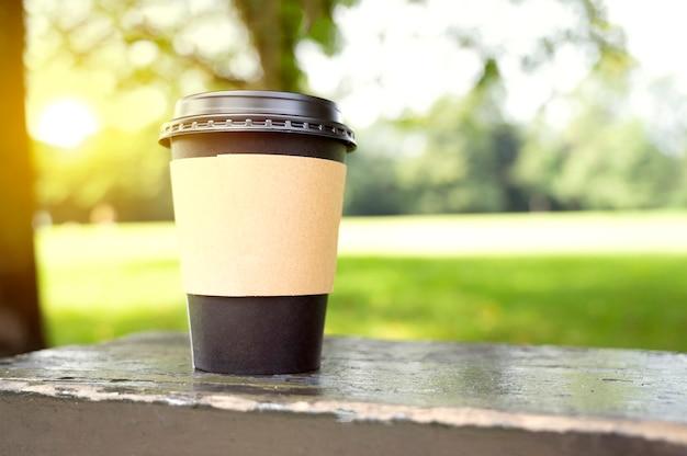 Taza desechable de café negro, taza de café para llevar en el parque