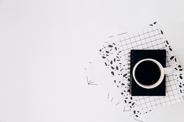 Taza y diario de café en los papeles del diseño contra el contexto blanco