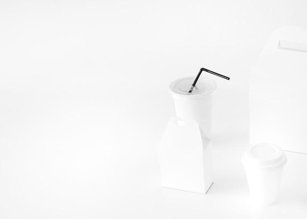 Taza de la disposición y paquete del alimento aislado en la superficie blanca