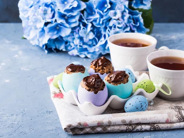 La taza dulce de pascua hornea copas en coloridas cáscaras de huevo en azul