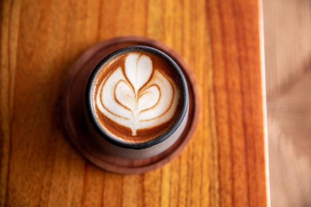 Taza elegante gris de moda de capuchino caliente con arte latte sobre fondo de mesa de madera