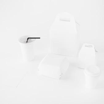 Taza de eliminación y paquete de alimentos se burlan sobre fondo blanco