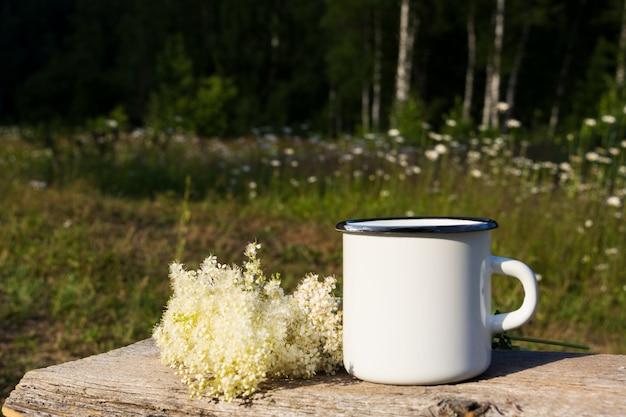 Taza de esmalte de fogata blanca con flores blancas