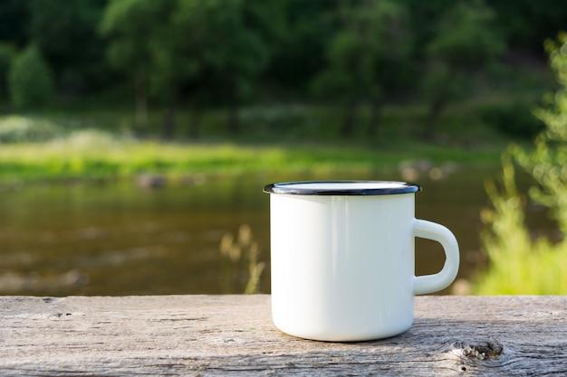 Taza de esmalte de fogata blanca vista al río