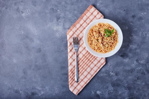 Una taza de espaguetis en salsa de tomate.