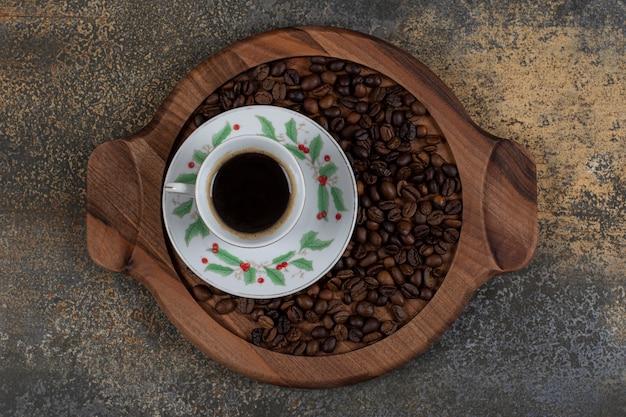 Taza de espresso aromático con granos de café sobre tabla de madera.