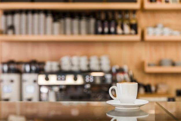 Taza de espresso fresco en el mostrador de vidrio