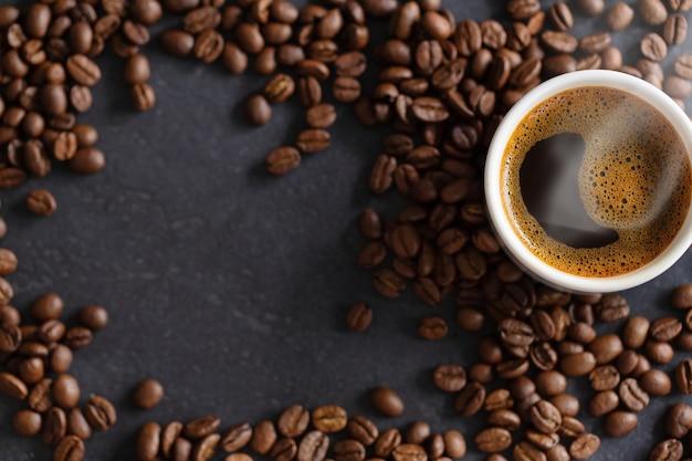 Taza de espresso humeante sobre fondo de granos de café. de cerca