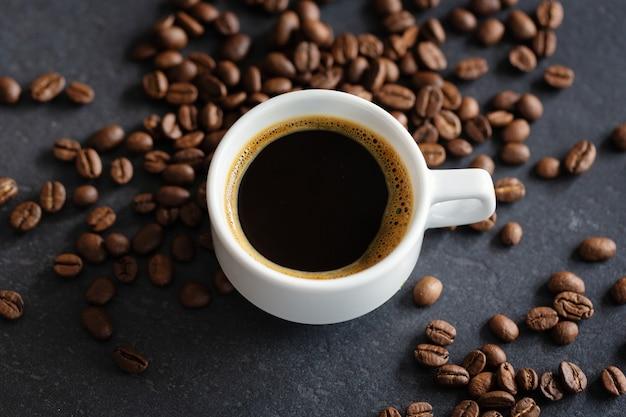Taza de espresso humeante sobre fondo gris. de cerca