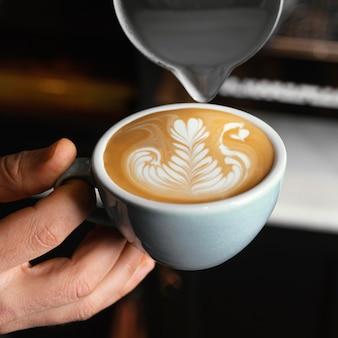 Taza de explotación de mano de primer plano con café