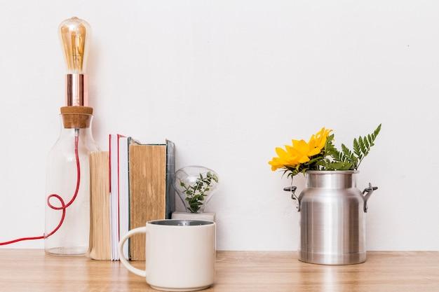 Taza flores en lata libros y lámpara en mesa