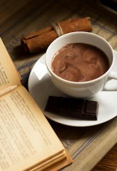 Taza de fragante bebida de cacao caliente en una bandeja de madera con un libro, canela, galletas y chocolate