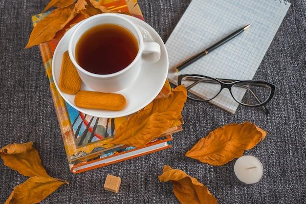 Taza de fragante té caliente entre hojas amarillas en una tela escocesa.