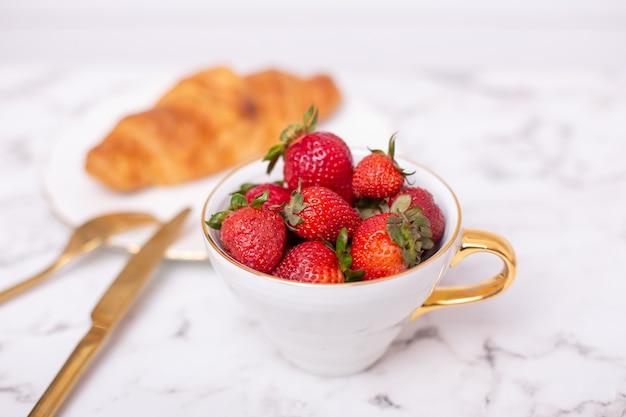 Taza con fresas frescas y croissant sobre fondo blanco.