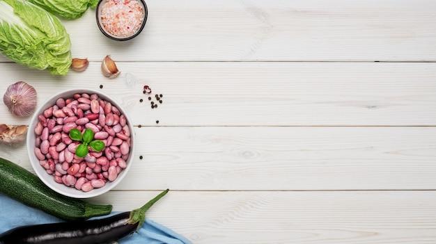 Taza con frijoles rojos activados decorada con hojas de albahaca, lista para cocinar