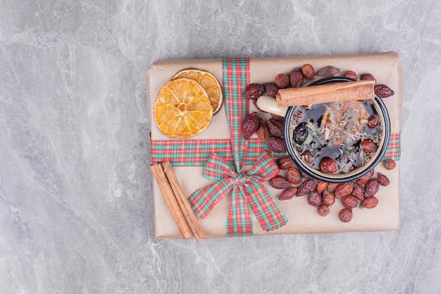 Una taza de glintwine con rodajas de canela y naranja