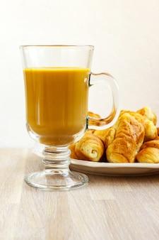 Taza de gluss de café con leche y plato blanco de croissants en madera clara de cerca. concepto de desayuno. enfoque selectivo. copia espacio