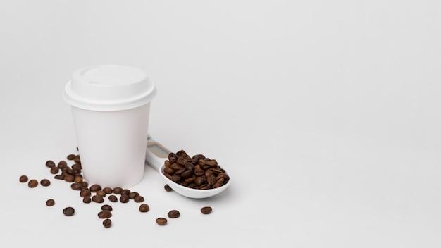 Taza y granos de café de ángulo alto