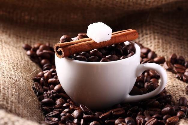 Taza con granos de café y canela en rama