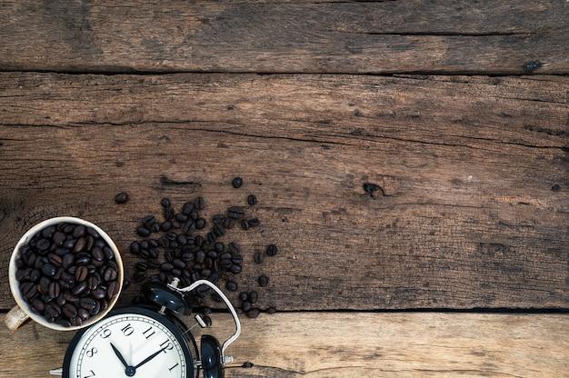 Taza de granos de café y un reloj sentado en el escritorio